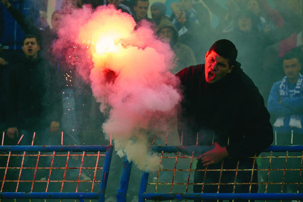 A fan holds a flare at a FK Zeljeznicar Sarajevo vs FK Sarajevo match. Photo by Robin Bharaj for Copa90.