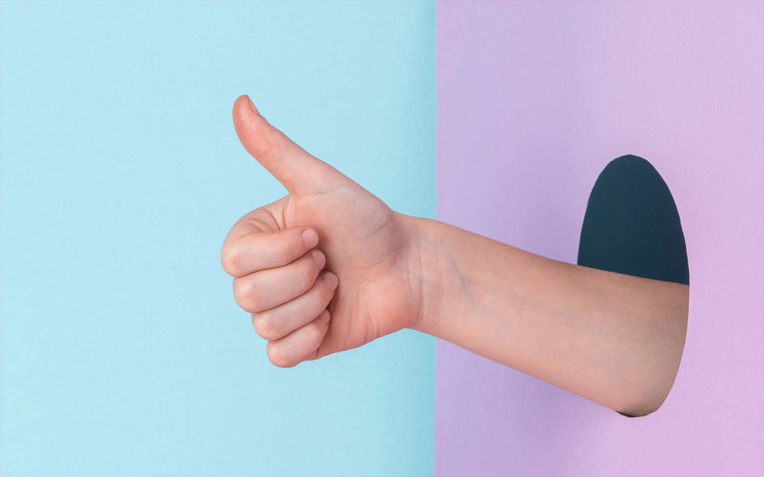 thumbs up emerging from circular hole in pink wall