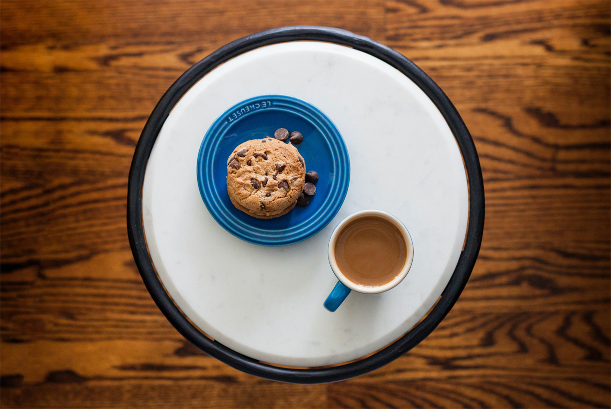 cookie on plate with cup of coffee on table aerial view