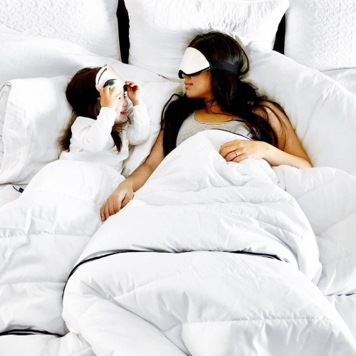 woman and child in bed wearing eyemasks