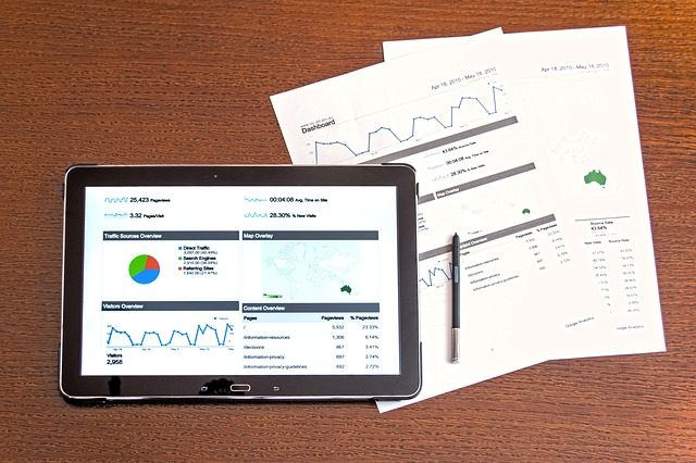 Stock image of tablet with analytics on the screen and two paper documents next to it.