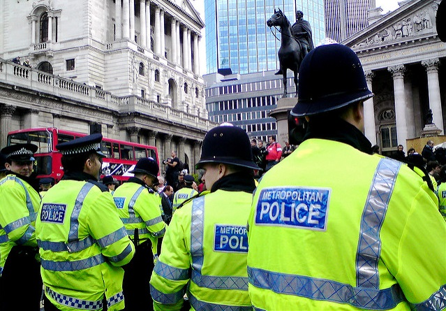 A police line in central Lodon, taken at an anti-capitalist demonstration in London in 2009. The officers in the photograph are shown from behind, wearing fluorescent yellow jackets emblazoned with Metropolitan Police.