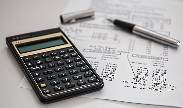 Stock image of a calculator lying next to a sheet of figures with some circled in pen. An uncapped pen lies on top of the papers.