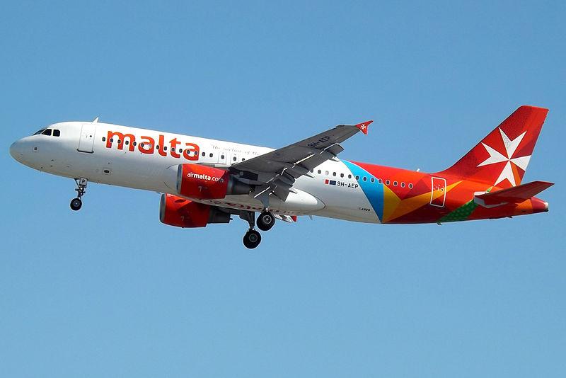 An Air Malta-branded aeroplane flies through a blue sky.