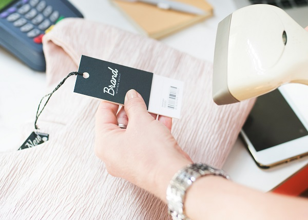 A hand holding up a clothing label entitled 'brand' and scanning it.