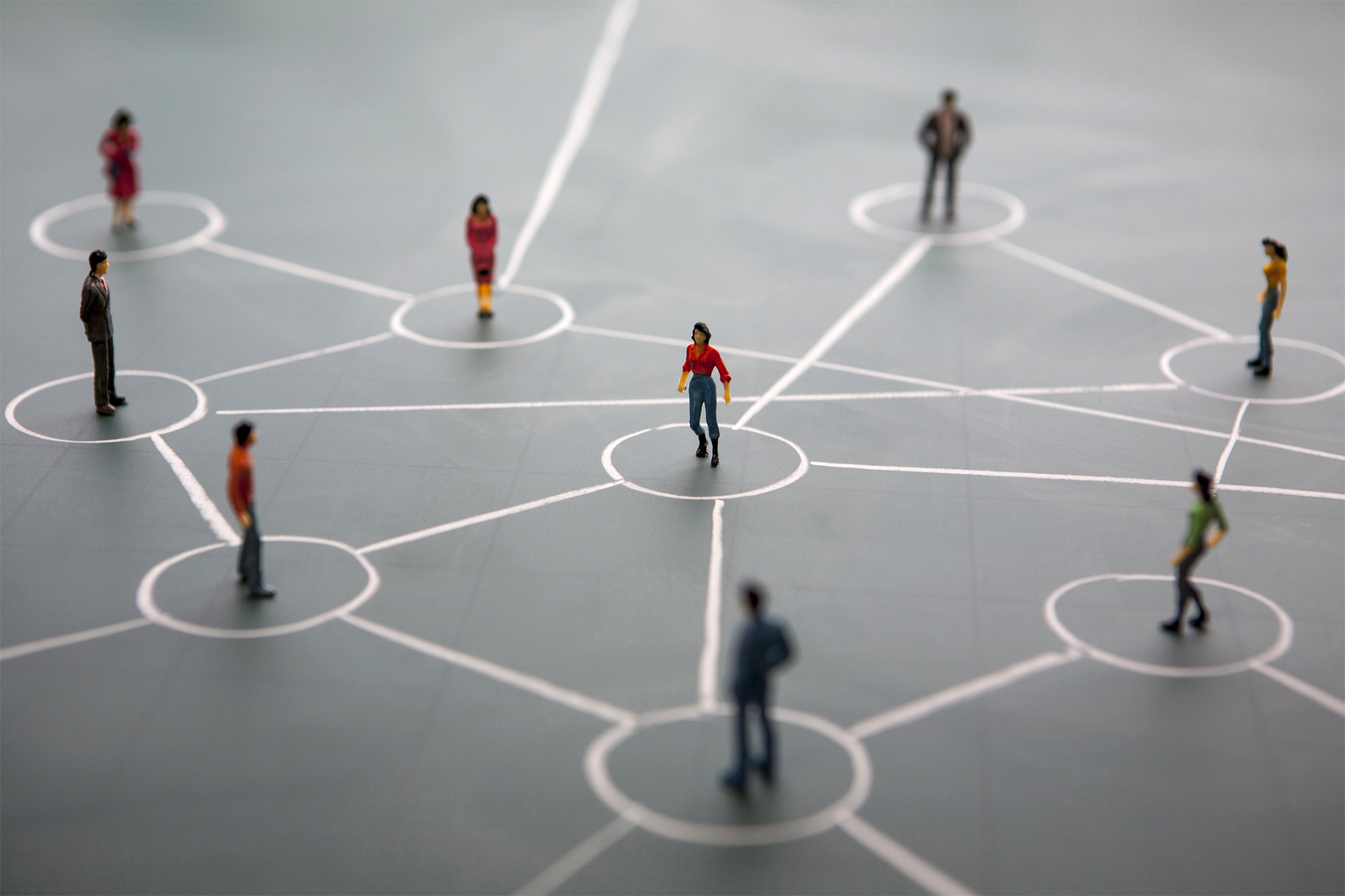 miniature model people standing on drawn chalk network