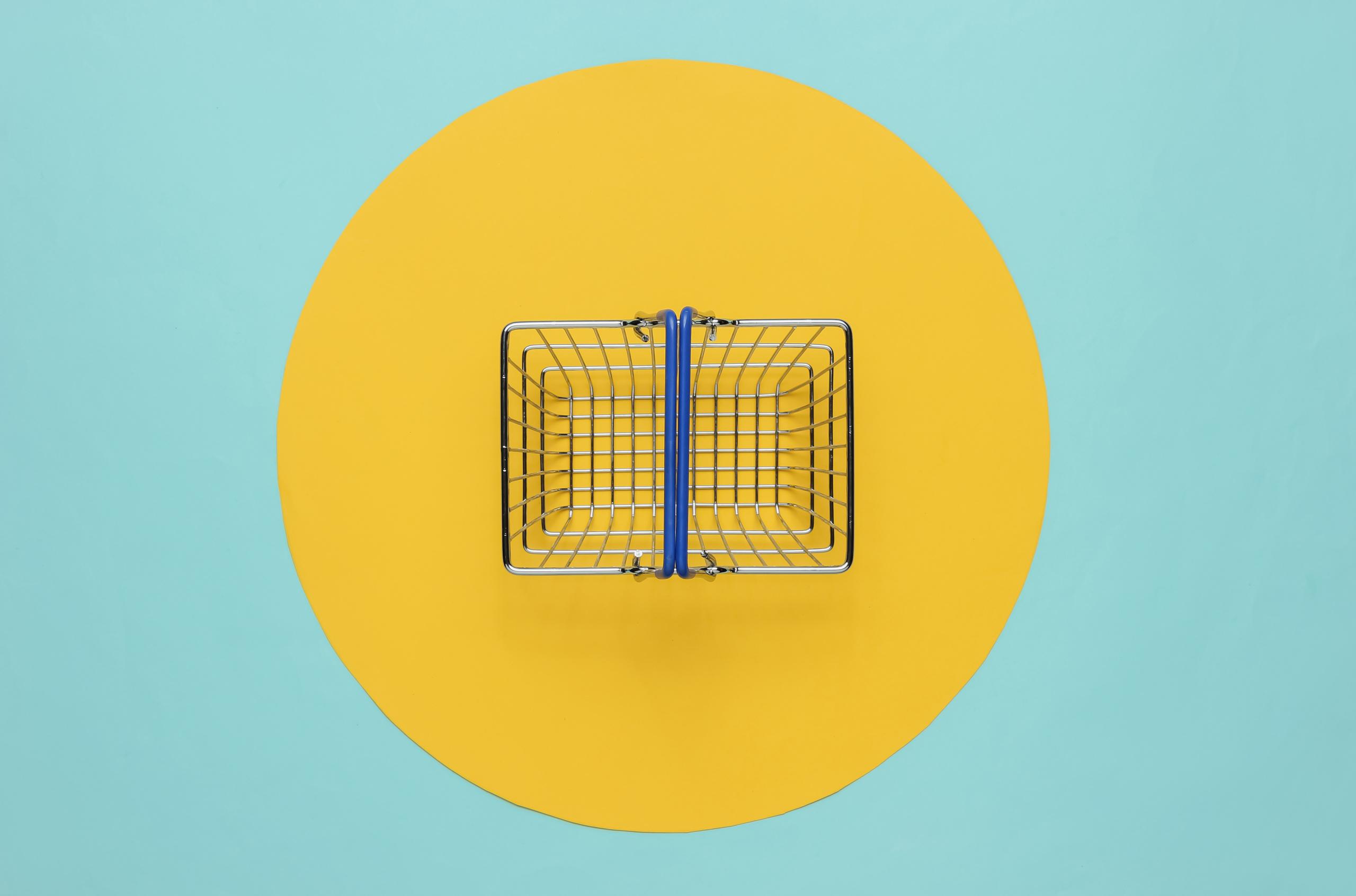 Mini-shopping-basket-on-blue-background-with-yellow-circle-scaled