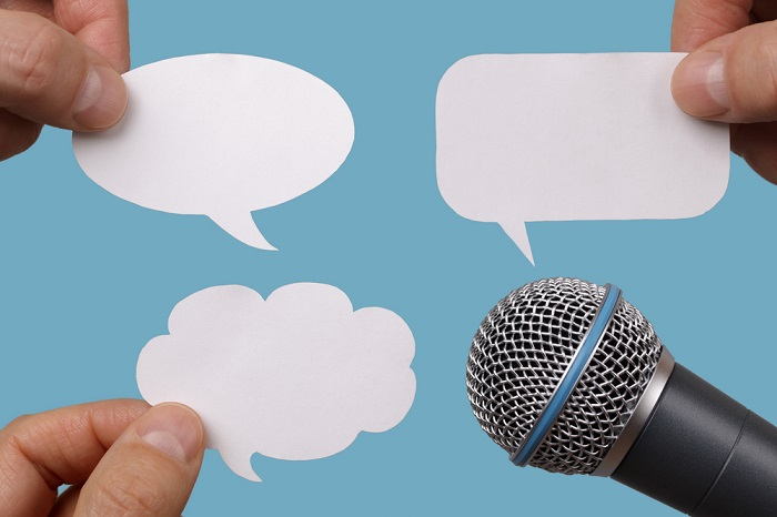 Microphone surrounded by speech bubbles
