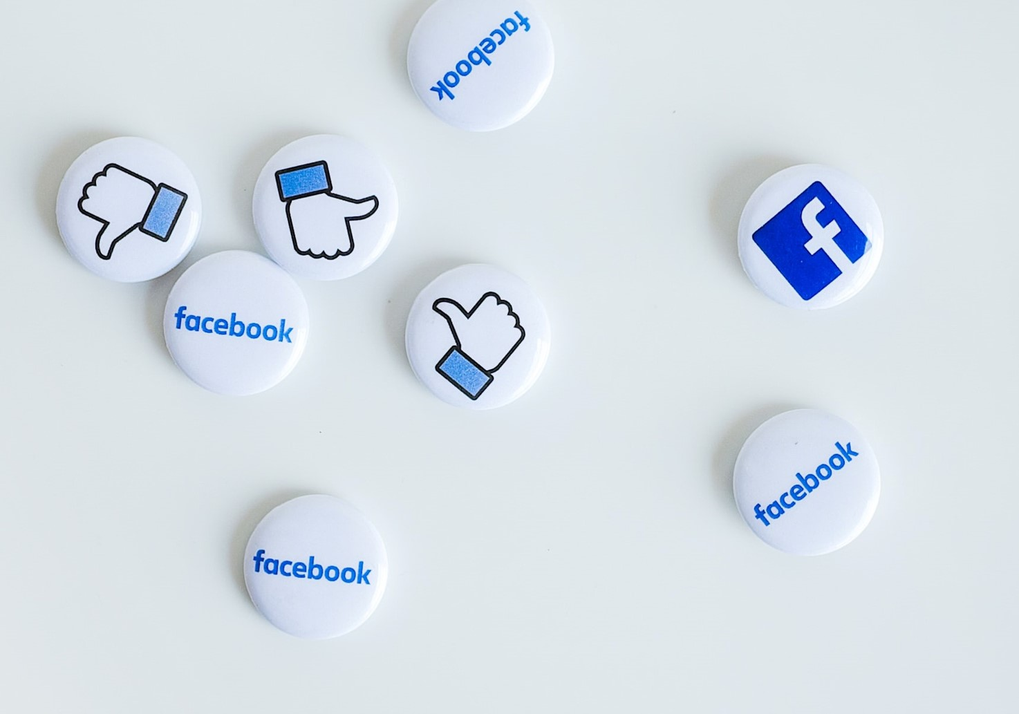 facebook icon pins badges scattered on white surface