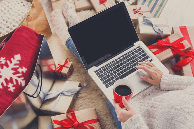 Person browsing on a laptop surrounded by winter holiday gifts