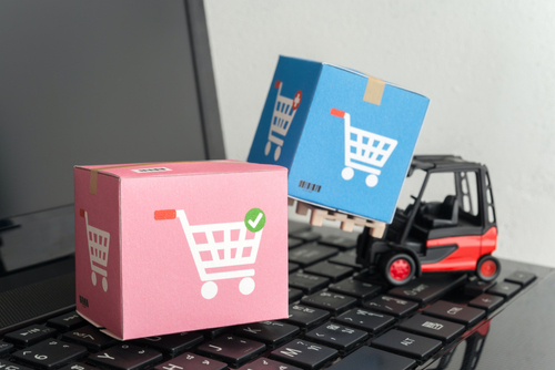 miniature forklift truck lifting boxes on laptop. via shutterstock