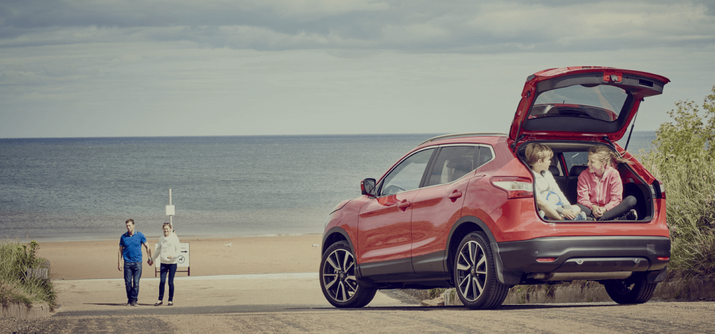 Red car on beach with children sitting in boot approached by mother and father