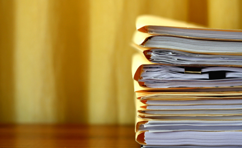 Pile of papers in document folders on a desk